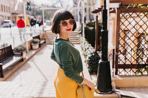 Entuzjastyczna kobieta o krótkich włosach, figlarnie spoglądająca przez ramię. plenerowe zdjęcie uroczej dziewczyny nosi żółte spodnie i okulary przeciwsłoneczne.