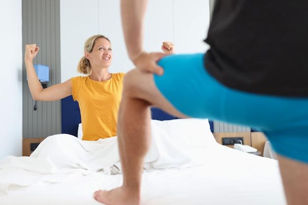 Entuzjastyczna kobieta siedzi w łóżku z rękami przed bielizną mężczyzny. koncepcja leczenia impotencji