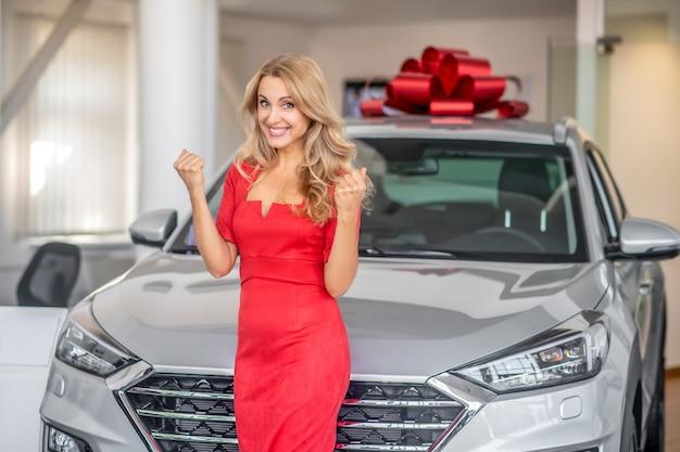 Entuzjastyczna kobieta w pobliżu jasnego nowego samochodu