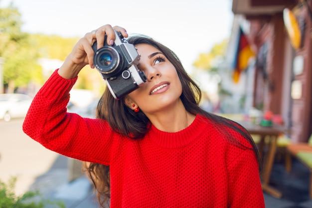 Entuzjastyczna kobieta z długimi włosami patrząc w górę, robiąc zdjęcia, ciesząc się niesamowitą architekturą starego europejskiego miasta. wiosna lub jesień. przytulny sweter z dzianiny w kolorze czerwonym. słoneczna pogoda. ciepłe kolory.