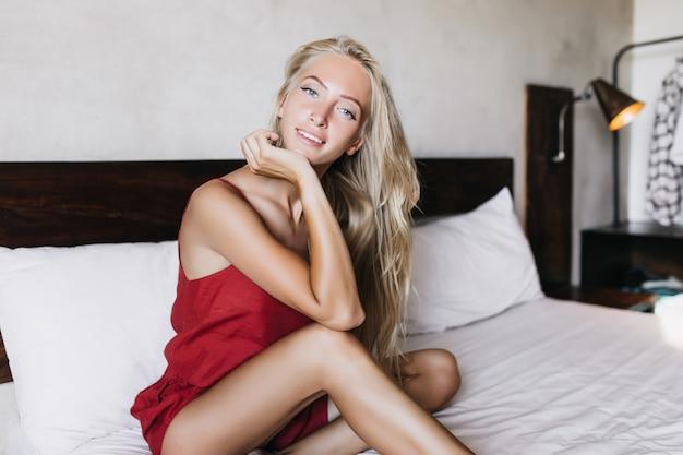 Entuzjastyczna kobieta z prostymi blond włosami siedzi na łóżku. kaukaski kobieta w piżamie stwarzających z wyrazem zainteresowania w sypialni.