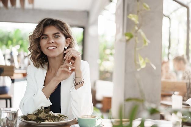 Entuzjastyczna kreatywna atrakcyjna bizneswoman zaintrygowana rozmowa o współpracowniku projektu w porze obiadowej siedzieć restauracja nowoczesna kawiarnia szczupły stół jeść sałatkę pić kawę uśmiechnięty zadowolony, spotkanie przebiega dobrze.