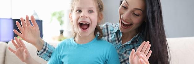 Entuzjastyczna mama i córka z pudełkiem siedzą na kanapie