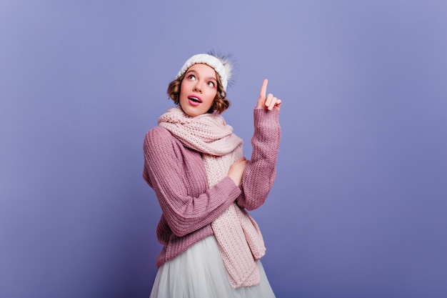 Entuzjastyczna młoda dama z krótkimi włosami pozuje w długim szaliku. wewnątrz zdjęcie fascynującej kobiety europejskiej w zimowym stroju na białym tle na fioletowej ścianie.