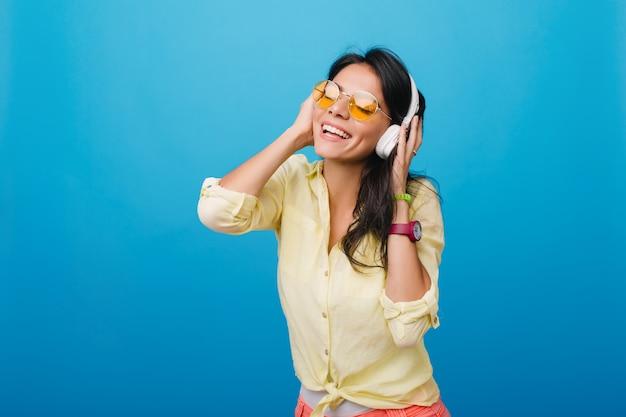 Entuzjastyczna młoda kobieta w stylowej żółtej koszuli i różowej bransoletce dotyka słuchawek podczas słuchania piosenki. kryty zdjęcie błogiej latynoskiej dziewczyny z błyszczącymi ciemnobrązowymi włosami.