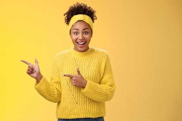 Entuzjastyczna młoda tysiącletnia czarna dziewczyna nie może uwierzyć w promocję prawdziwe szeroko otwarte oczy uśmiechnięte zdziwiona wygrana niesamowita szansa na loterię los wskazujący lewym palcem wskazujący na fajną okazję.