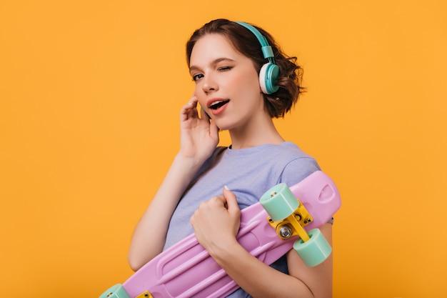 Entuzjastyczna modelka w dużych niebieskich słuchawkach żartobliwie pozuje z longboardem. urocza dziewczyna z deskorolka, uśmiechając się