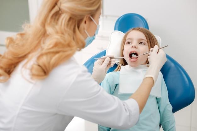 Entuzjastyczna odważna dziewczynka siedzi na fotelu dentysty i trzyma usta otwarte, podczas gdy lekarz patrzy na jej zęby