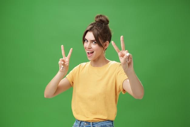 Entuzjastyczna, podekscytowana i wesoła odważna dziewczyna z tatuażem z zaczesanymi włosami i uroczą diasdemą pokazującą znaki pokoju, pochylającą się do tyłu, stojącą w chłodnej, energetyzującej pozie nad zieloną ścianą.