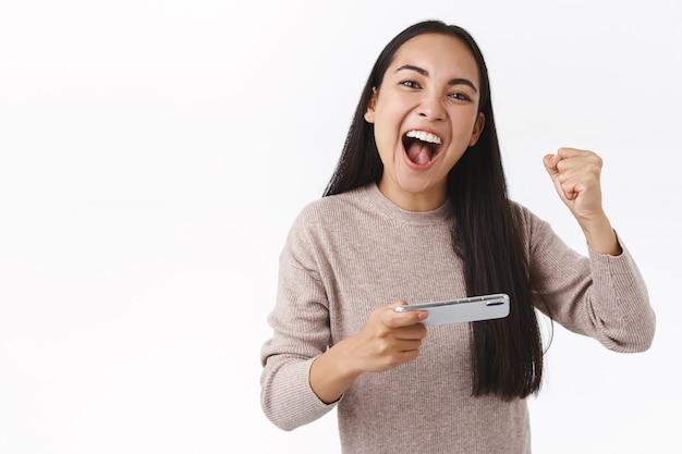 Entuzjastyczna przystojna, wesoła azjatycka młoda dziewczyna wygrywająca grę, pokonuje wynik, triumfuje pięścią i wrzeszczy tak, aby zachęcić siebie, trzymając smartfon poziomo, ukończ trudny poziom