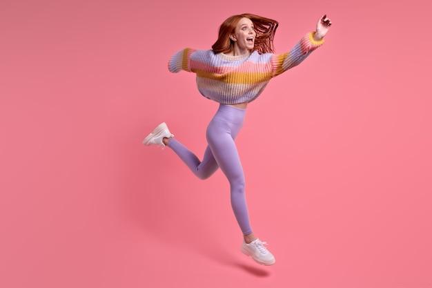 Entuzjastyczna ruda podekscytowana kobieta skok na czarny piątek zniżki nosić odzież w stylu casual strój na białym tle nad różowy kolor tła studio, portret. kopiuj przestrzeń