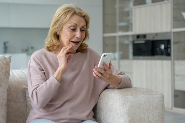 Entuzjastyczna starsza kobieta korzystająca ze smartfona pod wrażeniem sieci społecznościowych siedząca na kanapie w