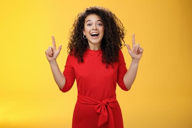Entuzjastyczna, szczęśliwa, kędzierzawa młoda europejska kobieta czuje się szczęśliwa, prezentując niesamowitą przestrzeń, podnosząc ręce w górę i uśmiechając się z zachwytem i podziwem na żółtym tle.