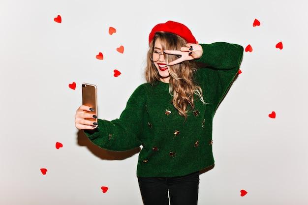 Entuzjastyczna uśmiechnięta kobieta w dużym zielonym swetrze robi selfie ze znakiem pokoju