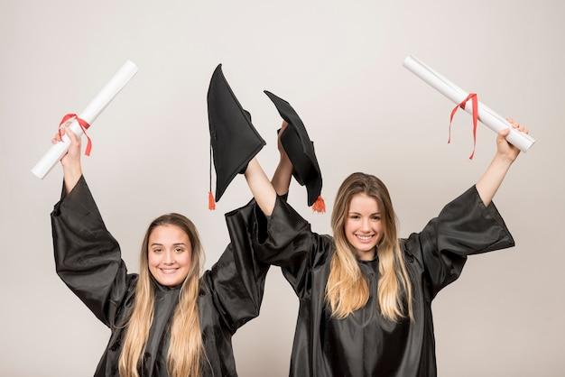 Entuzjastyczni absolwenci patrząc na kamerę