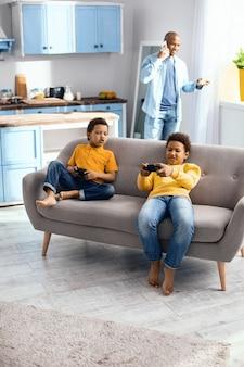 Entuzjastyczni gracze. przyjemni mali chłopcy siedzący na sofie i grający w gry wideo, mały chłopiec narzeka na swoją porażkę, podczas gdy ich ojciec rozmawia przez telefon