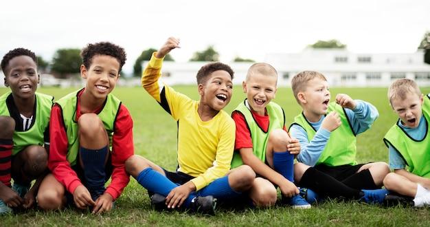 Entuzjastyczni piłkarzi siedzi na polu