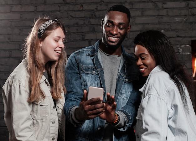 Entuzjastyczni wielorasowi przyjaciele patrząc na telefon