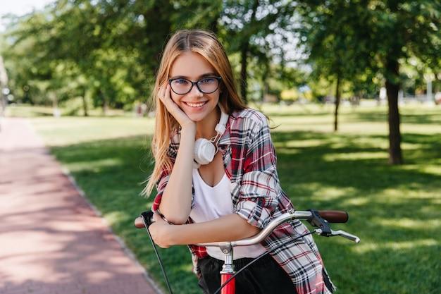 Entuzjastycznie nastawiona dziewczynka kaukaski w ślicznych okularach siedzi na rowerze. zewnątrz zdjęcie radosnej modelki pozuje z przyjemnością w zielonym parku.