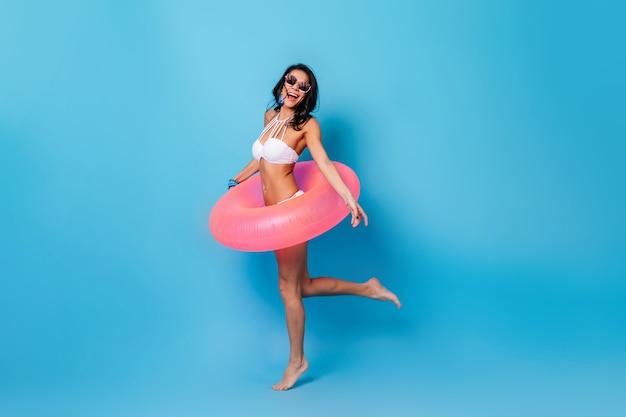 Entuzjastycznie opalona kobieta stojąca na niebieskim tle