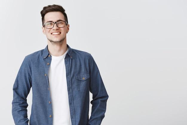 Entuzjastycznie uśmiechnięty mężczyzna szuka szczęścia w okularach i ubranie