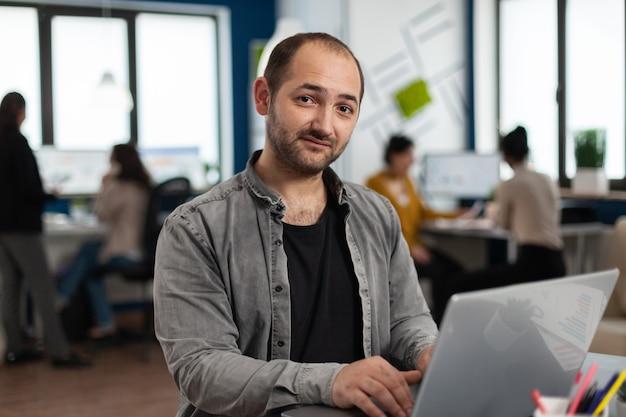 Entuzjastyczny biznesmen piszący raport siedzący przy stole w nowoczesnym biurze firmy startupowej