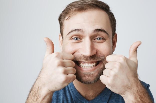 Entuzjastyczny brodaty facet pokazuje kciuki do góry szczęśliwy