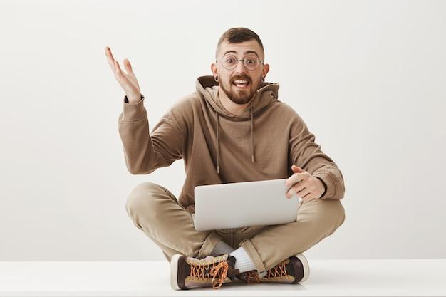 Entuzjastyczny facet dyskutuje o czymś siedząc na skrzyżowanych nogach z laptopem