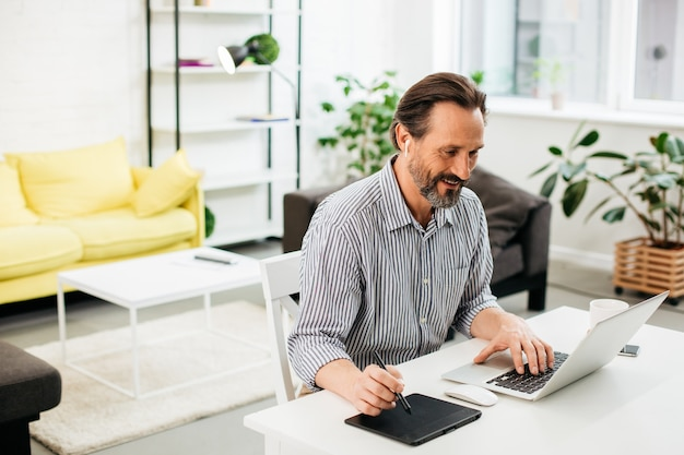 Entuzjastyczny mężczyzna w średnim wieku pracujący na swoim laptopie w domu i korzystający z tabletu rysunkowego, noszący bezprzewodowe słuchawki i patrząc na ekran laptopa