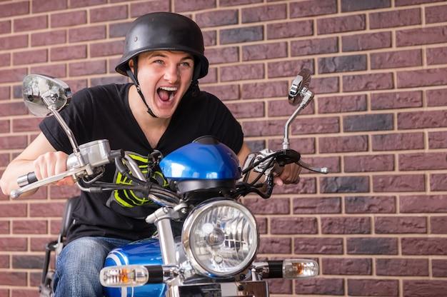 Entuzjastyczny młody człowiek jadący na motocyklu krzyczy, pędząc przed ceglaną ścianą w kasku w stylu retro