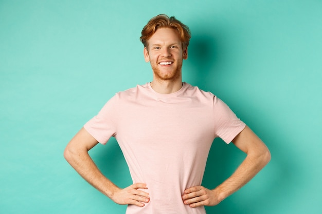 Entuzjastyczny młody człowiek o rudych włosach, ubrany w t-shirt, stojący szczęśliwy i dumny z rękami na chmielu, stojący na turkusowym tle.