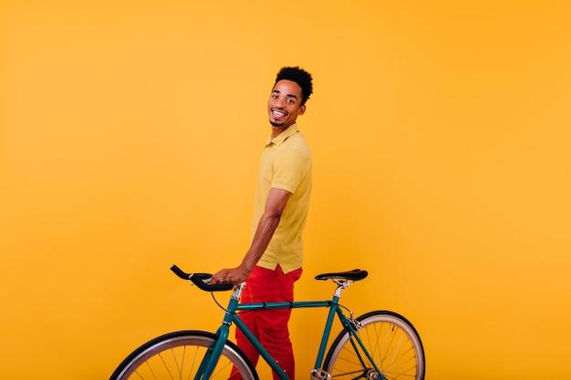Entuzjastyczny murzyn z wesołym uśmiechem pozuje z rowerem. kryty zdjęcie radosnego afrykańskiego modelu mężczyzny stojącego z rowerem.