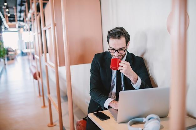 Entuzjastyczny przystojny biznesmen kaukaski brodaty w garniturze iw okularach siedzi przy stole, pije kawę i kończy raport. wnętrze firmy.