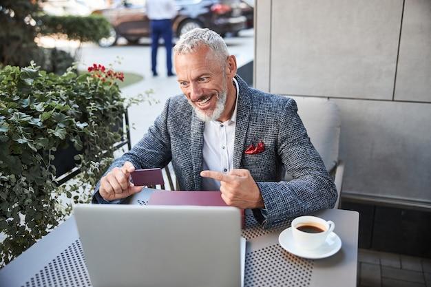 Entuzjastyczny starzejący się mężczyzna wskazujący na plastikową kartę w dłoni podczas wideorozmowy