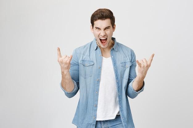 Entuzjastyczny szczęśliwy człowiek bawiący się, pokazujący rock-n-rollowy gest