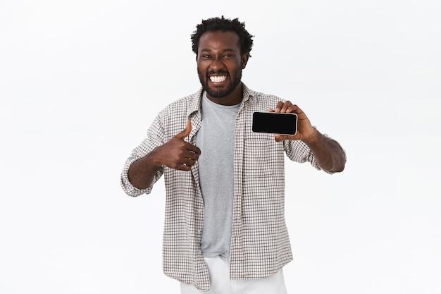 Entuzjastyczny uśmiechnięty szczęśliwy afroamerykanin zdumiony niesamowitą nową aplikacją