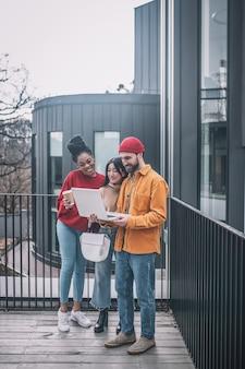 Entuzjazm. facet z laptopem i dwie dziewczyny z kawą stoją razem na zewnątrz w pobliżu biura uśmiechając się patrząc na ekran