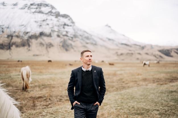 Epicki męski portret na polu żółtej trawy wśród pasących się koni na tle ośnieżonej góry