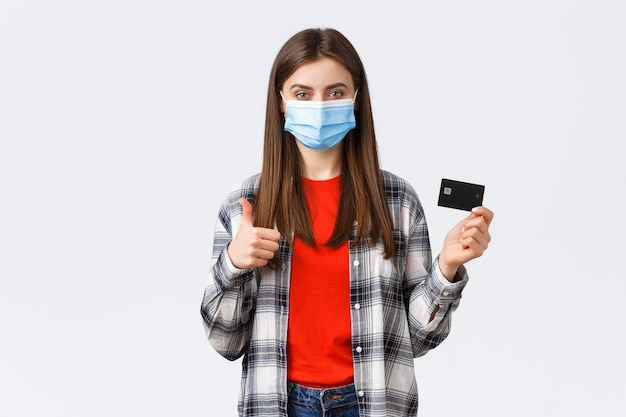Epidemia koronawirusa, praca w domu, zakupy online i koncepcja płatności zbliżeniowych. zadowolona kobieta w masce medycznej zaleca używanie karty kredytowej podczas pandemii, kciuk w górę