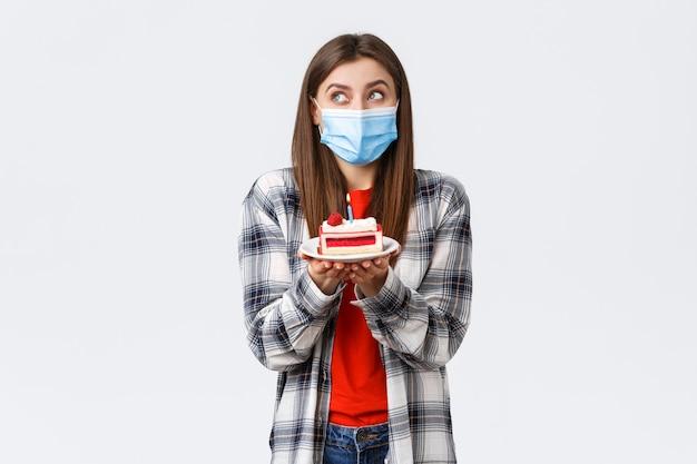 Epidemia koronawirusa, styl życia podczas koncepcji obchodów dystansu społecznego i świąt. marzycielska ładna dziewczyna w masce medycznej, marzycielski spojrzenie w górę, obrazowanie życzeń jako trzymający tort urodzinowy ze świecą.