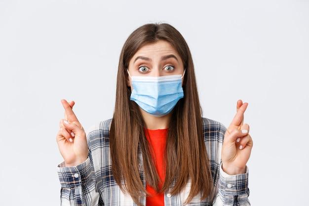 Epidemia koronawirusa, wypoczynek na koncepcji kwarantanny, dystansu społecznego i emocji. pełna nadziei urocza dziewczyna w masce medycznej oczekująca dobrych wieści, uwierz, że marzenie się spełniło, trzymaj kciuki jako życzenie