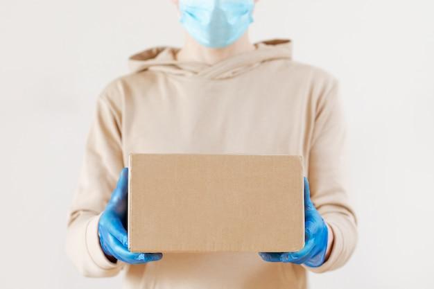 Epidemiczny koronawirus. kawa, pakiet fast foodów. bezdotykowa dostawa żywności. kurier w rękawiczkach i masce przechowuje ekologiczne opakowania. zostań w domu, bądź bezpieczny