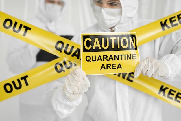 Epidemiolodzy mężczyzna i kobieta w odzieży ochronnej przebywają na ograniczonym obszarze ze znakiem niebezpieczeństwa. żółta linia keep out quarantine. wejście jest zabronione w strefie kwarantanny. koronawirus (covid-19.