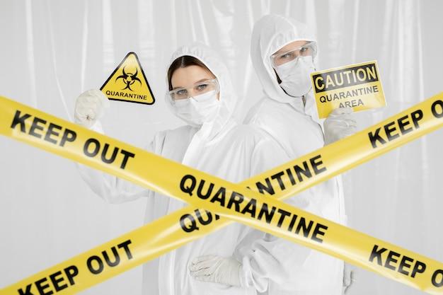 Epidemiolodzy, mężczyzna i kobieta w odzieży ochronnej, znajdują się na obszarze o ograniczonym dostępie ze znakiem ostrzegawczym