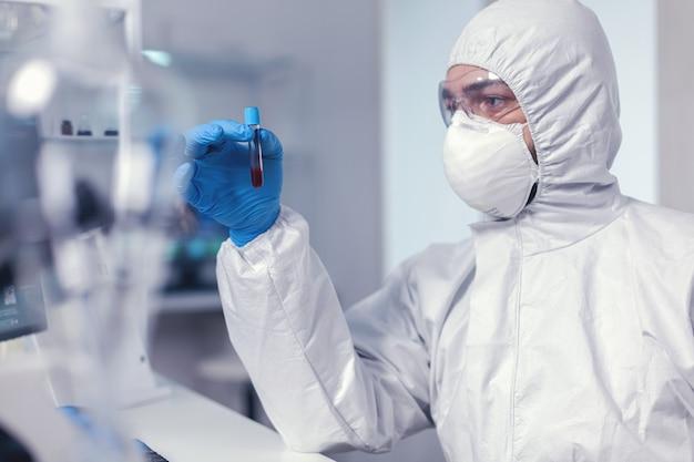 Epidemiolog analizujący krew w probówce zakażonej koronawirusem ubrany w strój ochronny. lekarz pracujący z różnymi bakteriami i tkankami, badania farmaceutyczne nad antybiotykami przeciwko covid19.