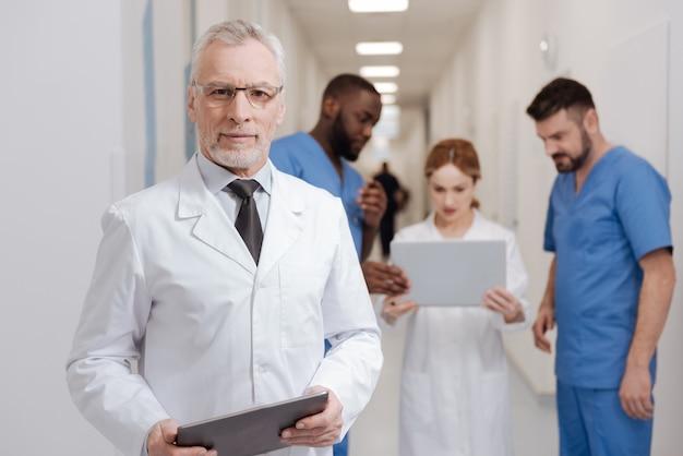 Epoka nowoczesnych technologii. charyzmatyczny, brodaty, rozbawiony pediatra cieszy się pracą w klinice i trzyma tablet, podczas gdy inni koledzy pracują z laptopem w tle