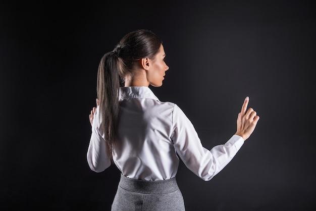 Era cyfrowa. mądra, miła pewna siebie kobieta stojąca na czarnym tle i korzystająca z inteligentnych technologii podczas pracy