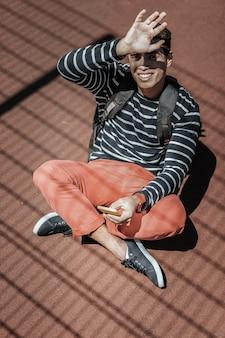 Era cyfrowa. widok z góry wesoły optymistyczny facet trzymający telefon i zasłaniający oczy przed słońcem