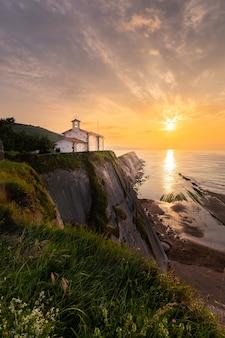 Ermitaż san telmo na szczycie klifu plaży itzurun w zumaia, kraj basków.