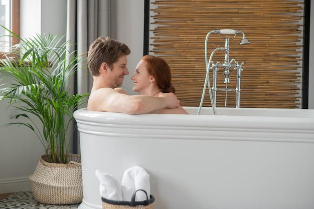 Erotyczne chwile. mężczyzna i kobieta kąpią się razem i wyglądają na podekscytowanych
